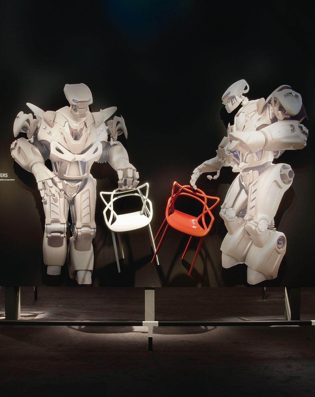 Un angolo espositivo dello stand Kartell al Salone del Mobile nel 2009 (Milano). Due robot presentano la nuova sedia Masters. / Decoration panel at the Kartell booth, Salone del Mobile, Milan, 2009. Two androids introduce the new chair Masters.