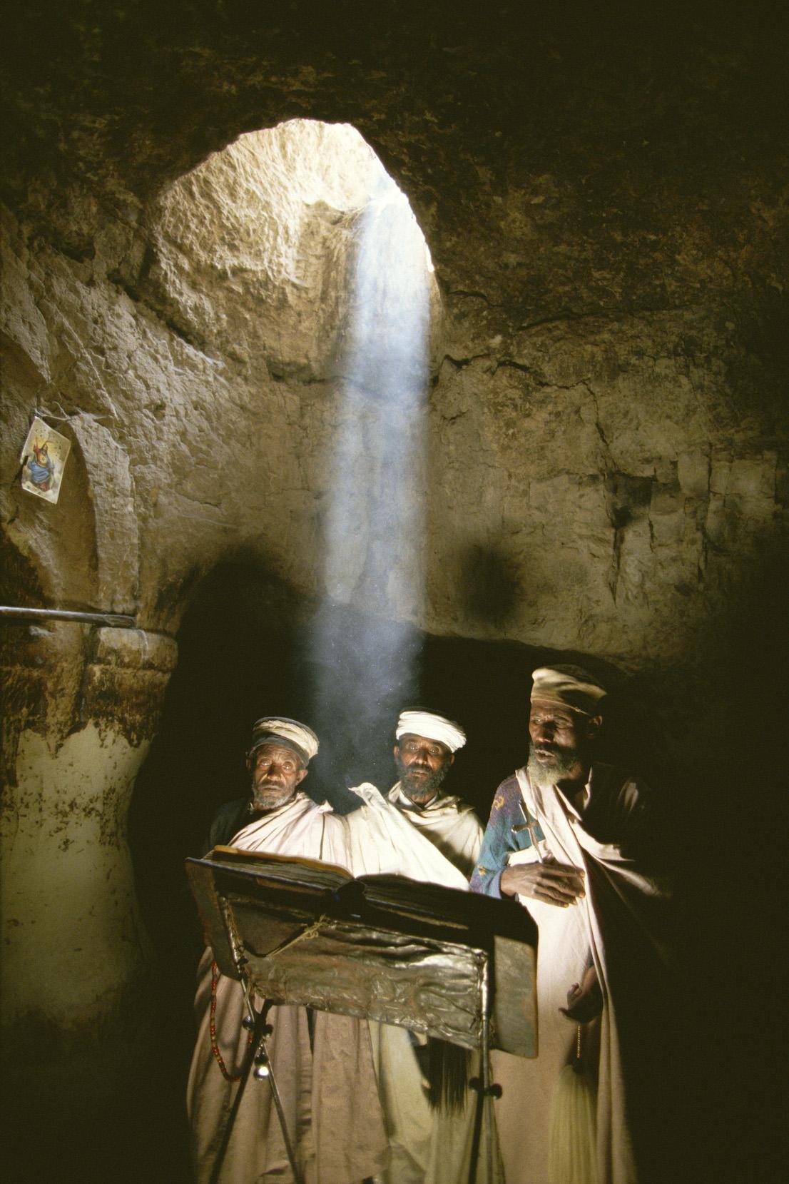 Foto di Kazuyoshi Nomachi. Un gruppo di sacerdoti prega nella chiesa di Abuna Aron poco dopo mezzogiorno, quando da un oculo della volta i raggi del sole scendono a perpendicolo nella chiesa scavata nella roccia. Nei pressi di Lalibela, Etiopia, 1996.