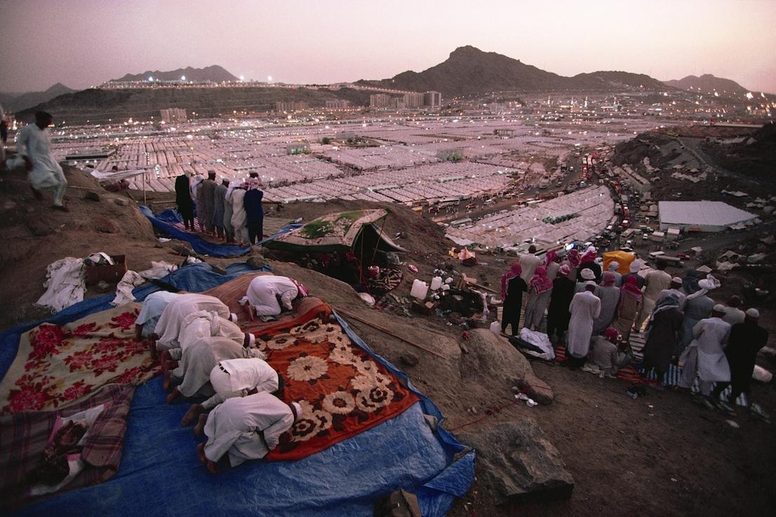Foto di Kazuyoshi Nomachi. I pellegrini recitano il Maghrib dopo il tramonto nella tendopoli di Mina, allestita per accoglierli durante l'Hajj. La Mecca, Arabia Saudita 1995.