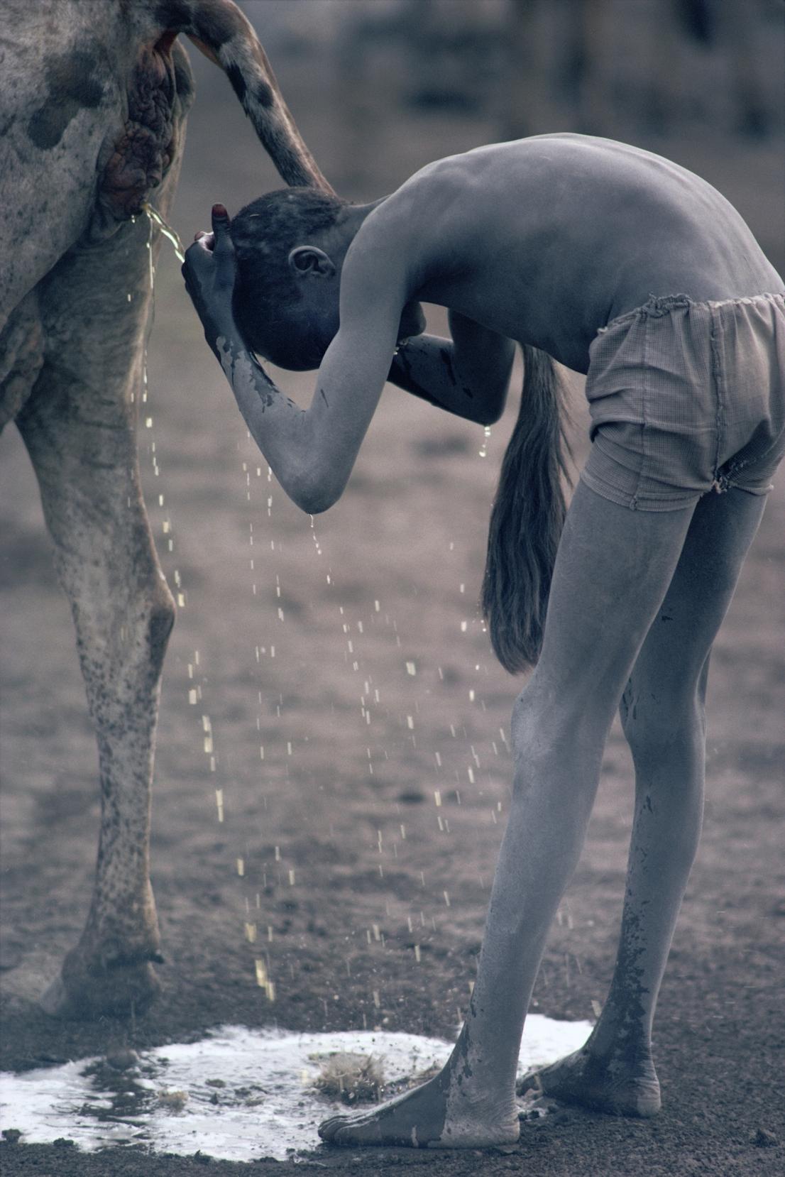 Foto di Kazuyoshi Nomachi. Un ragazzo Nuer si lava i cappelli con l'urina di mucca Jonglei, Sudan del Sud, 1981.