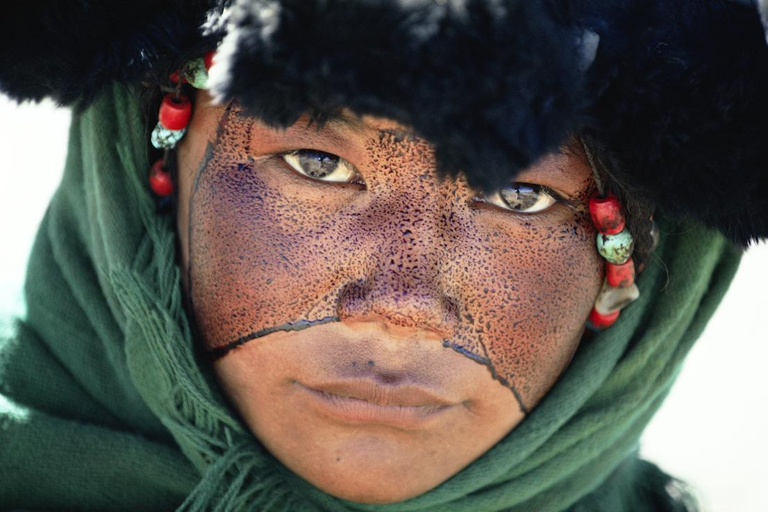 Foto di Kazuyoshi Nomachi. Una ragazza nomade con il volto cosparso di una sostanza protettiva durante un pellegrinaggio, Tibet, Cina, 1990.