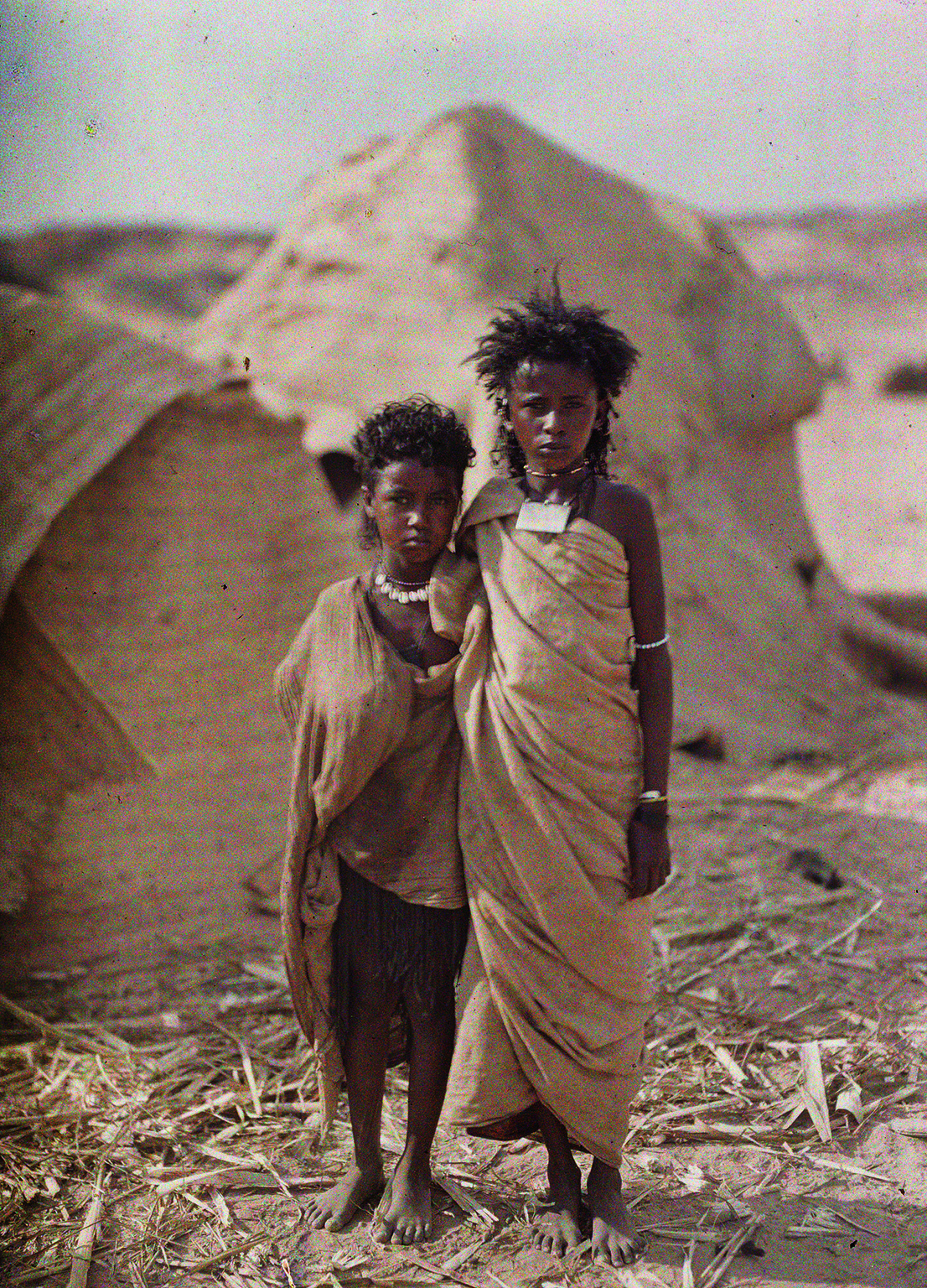 Albert Kahn, Les Archives de la Planète, Auguste Léon. Egypt, Assuan, two young Bishari- (Nubier-) women in front of their dwelling. January 1914. © Musée Albert-Kahn, Département des Hauts-de-Seine.