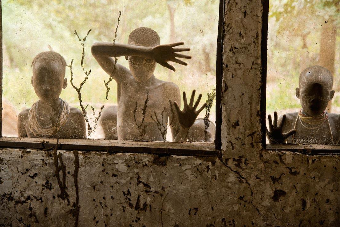 Bambini della tribù Kara che guardano attraverso le finestre, Omo Valley, Ethiopia, 2013