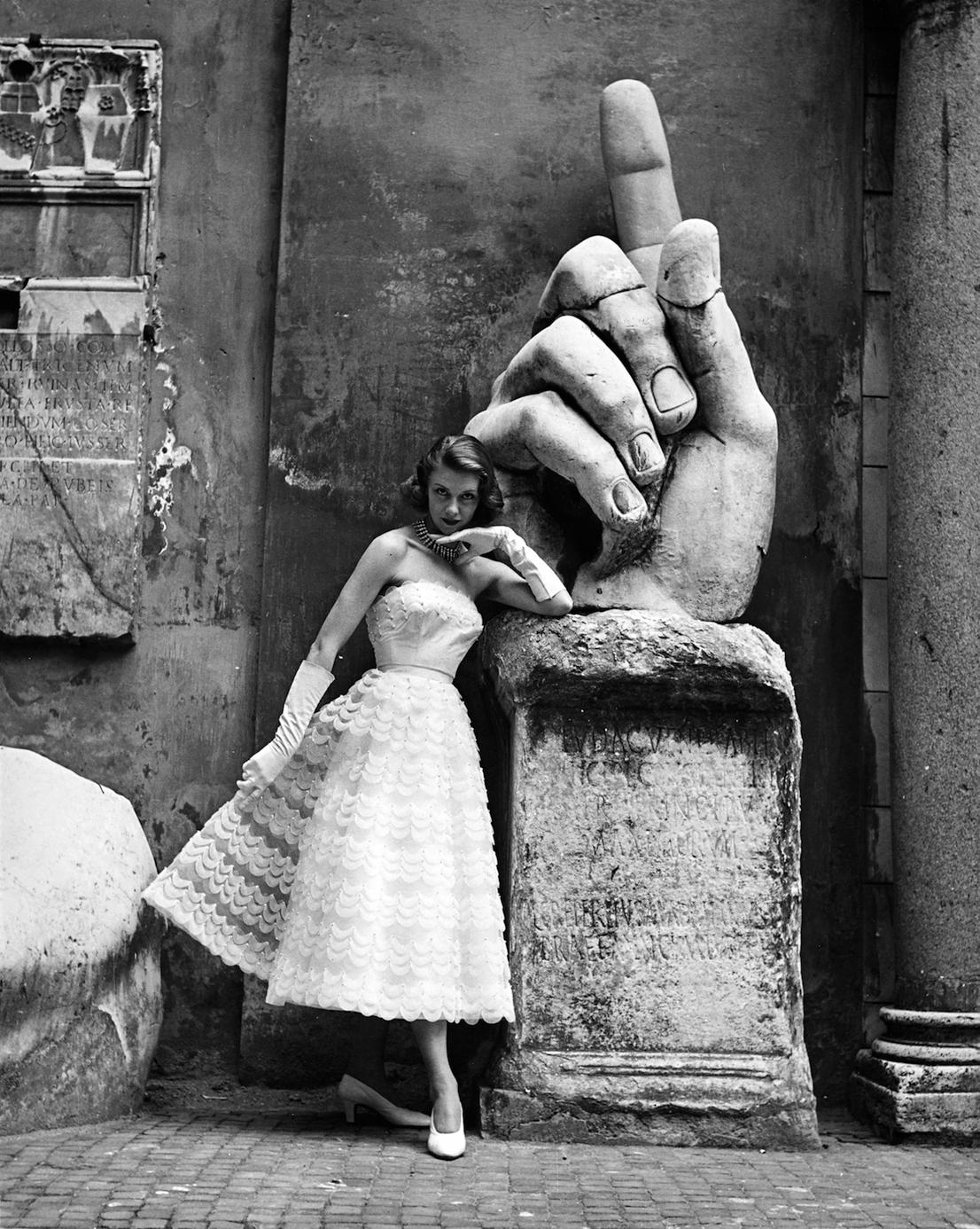 La modella, fotografata ai Musei Capitolini davanti alla mano della statua monumentale di Costantino I, indossa un modello delle Sorelle Fontana (pubblicata sulla rivista La Donna) Foto di Regina Relang, 1952. Courtesy Münchner Stadtmuseum, Sammlung Fotografie, Archiv Relang.