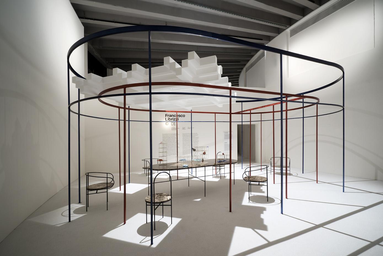 """La stanza """"D1"""" di Francesco Librizzi è uno spazio ellittico formato da recinti concentrici fatti di esili colonne di metallo colorato, un modo di raccontare la scoperta dello spazio domestico e il ruolo dell'architettura di mediazione tra paesaggio, spazio domestico e oggetti."""