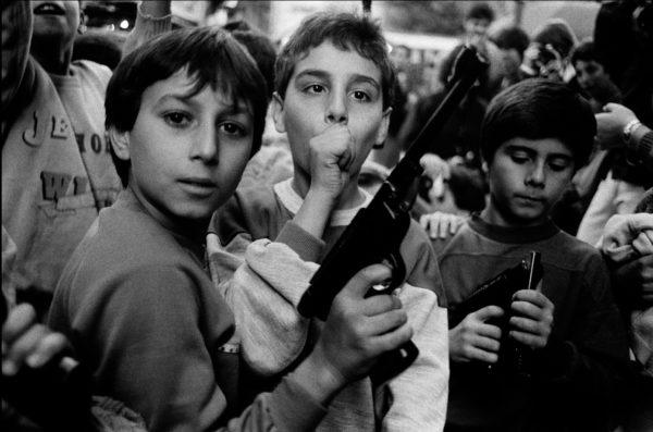 Letizia Battaglia, Festa del giorno dei morti. I bambini giocano con le armi. Palermo – 1986. Courtesy: Letizia Battaglia.