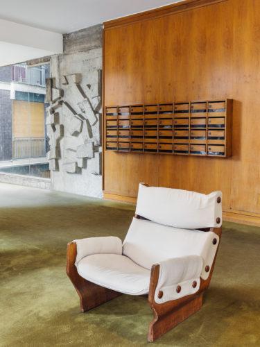 Via Melzi d'Eril 29, Ruggero Farina Morez, 1965. Il pannello artistico alle pareti, in cemento, è di Gino Cosentino, mentre la poltrona è di Osvaldo Borsani.