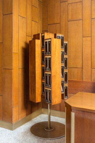 Via Vincenzo Monti 41, Luigi Mattioni, 1968. Mobile girevole per la posta in legno e pavimento in granito Bianco Montorfano.