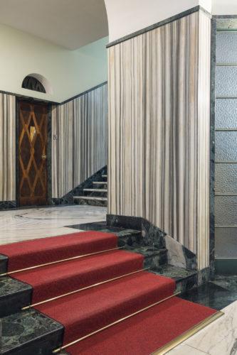 Via San Vittore 32, Vittorio Verganti, 1935-37. Rivestimento della parete in marmo Zebrino, a righe grigie e bianche. Pavimento in marmo Bianco Carrara Venato e in oficalcite Verde Alpi.