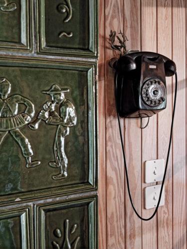 Particolare dell'interno con la decorazione a formelle di terracotta e il telefono originale. Foto: © Marcello Mariana.