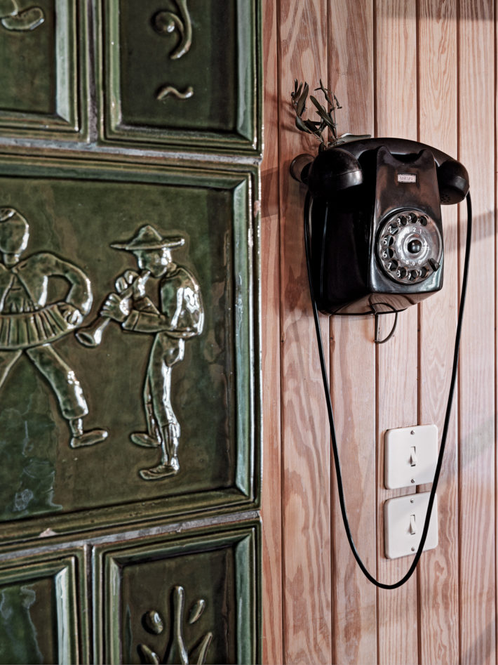 Detail of the interior with the terracotta-tile decoration and the original telephone. Photo:© Marcello Mariana.