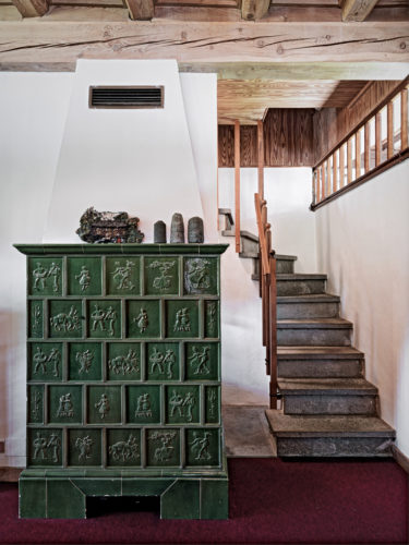 Thun stove clad in ceramic tiles on the ground floor and the stone staircase that leads to the second floor. Photo:© Marcello Mariana.