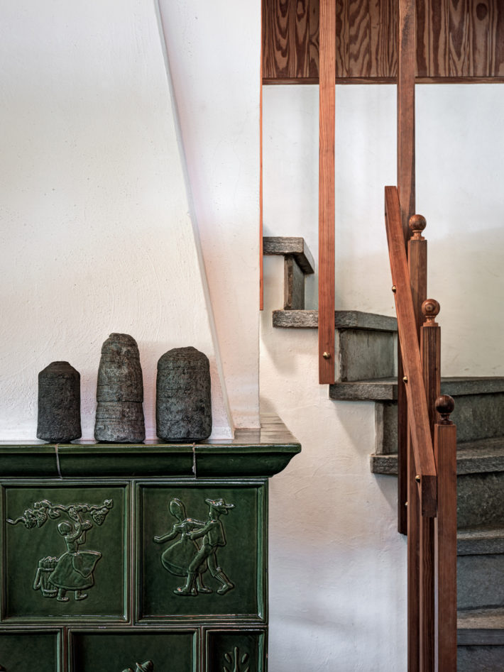 Stufa Thun rivestita in ceramica al piano terreno e la scala in pietra che conduce al primo piano. Foto: © Marcello Mariana.