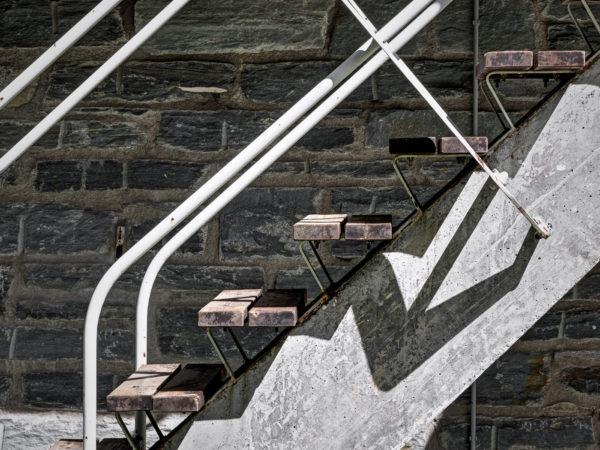 Particolari della scala esterna con struttura a trampolino costituita da una trave di cemento armato a sezione variabile, tredici pedate in legno appoggiate su due nastri metallici continui e ringhiera in tubolare metallico bianco. Foto: © Marcello Mariana.