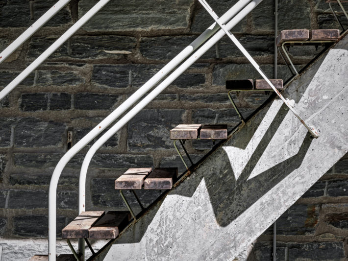 Details of the external staircase with a springboard structure made of a reinforced-concrete beam with a variable cross section, thirteen wooden treads resting on two continuous metal strips and handrails of white metal tubing. Photo:© Marcello Mariana.